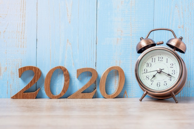 2020 happy new year  with retro alarm clock and wooden number.