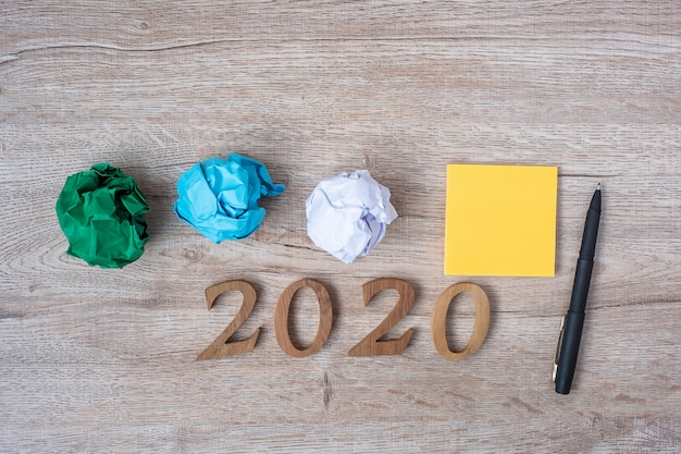 2020 happy new year with yellow note and crumpled papers