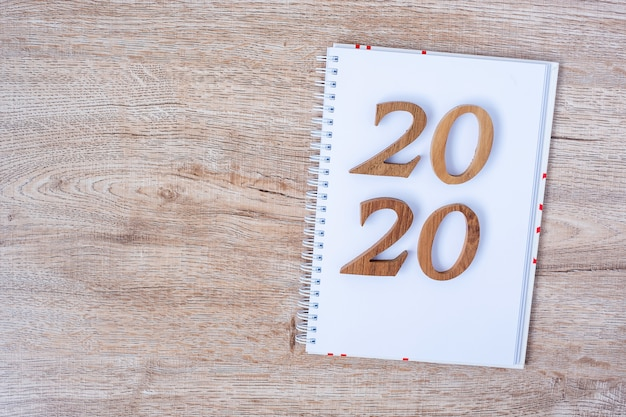 2020 happy new years with blank notebook for text and wooden number