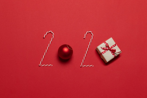 2020 inscription from various decorated objects classic red glass baubles ball, candy cane on a red background