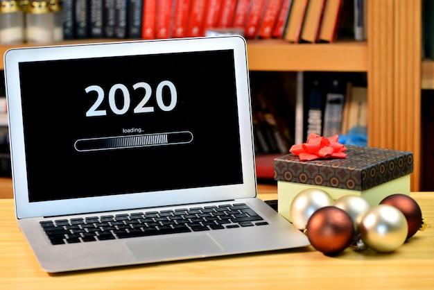 На столе елочные украшения, подарочная коробка и ноутбук с текстом - 2020 loading
