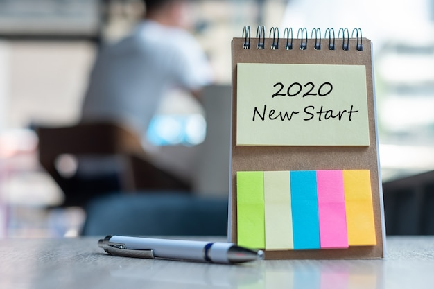 2020 new start word on note paper with pen on wooden table