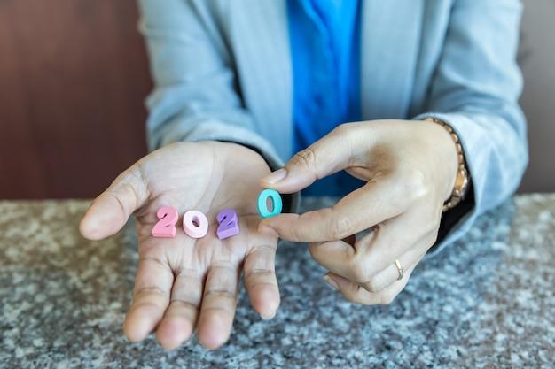 2020 новый год и концепция бизнес-планирования. закройте вверх коммерсантки держа красочный деревянный номер в ее руке.