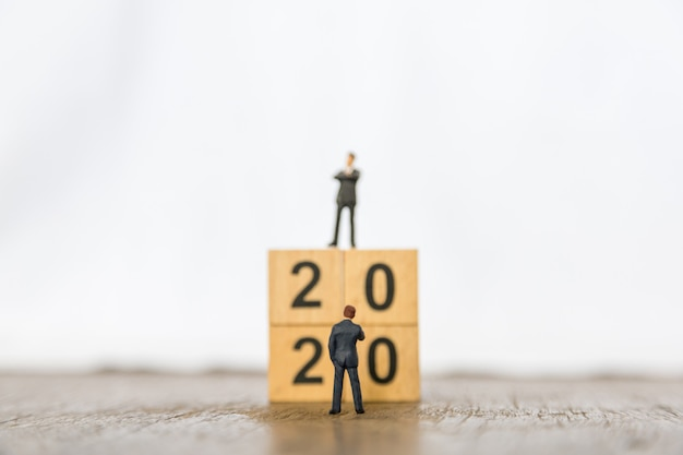 2020 new year and business planning . close up of two businessman miniature figure standing in front of  stack of wood number blocks