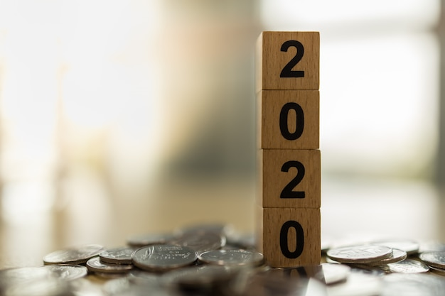 2020 new year, business, saving and planning concept. close up of stack of wooden number block toy on pile of coins with copy space