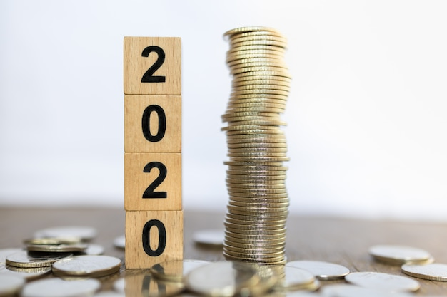 2020 new year, business, saving and planning concept. close up of stack of wooden number block toy with stack of coins on wood table and white background with copy space