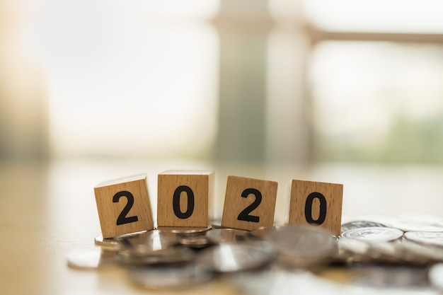 2020 new year, business, saving and planning concept. close up of wooden number block toy on pile of coins with copy space