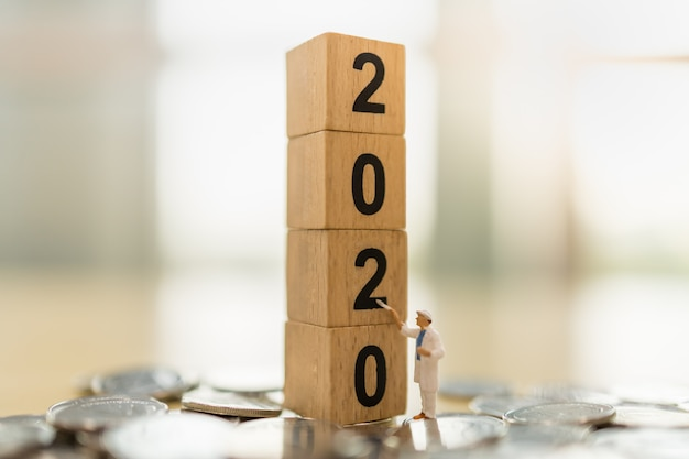 2020 new year, business, saving and planning concept. close up of worker miniature figure standing and painting  on stack of wooden number block toy on pile of coins with copy space