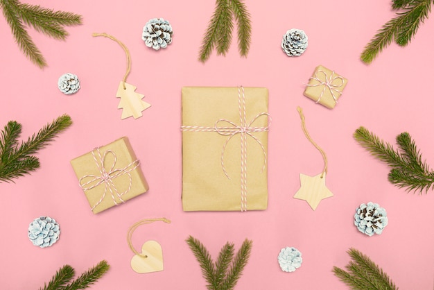 2020 new year composition. stylish decor concept, christmas wooden toy, kraft paper gift box, fir cones branches on pink