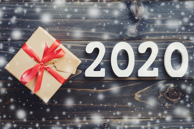 2020 new year concept : 2020 wood number and brown gift box with snow on wood table background.