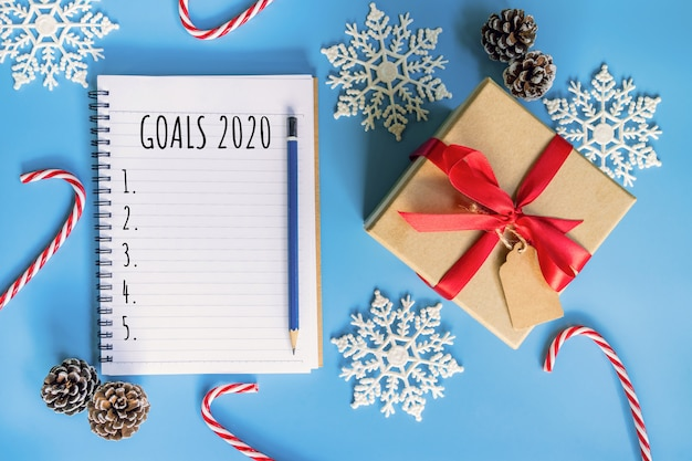 2020 new year concept. goals 2020 list in notepad, gift box and christmas decoration on blue pastel color with copy space