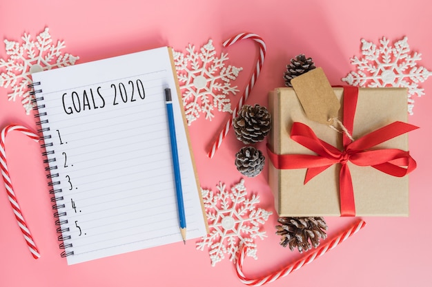 2020 new year concept. goals 2020 list in notepad, gift box and christmas decoration on pink pastel color with copy space