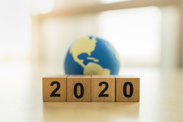 2020 new year , global and business concept. close up of stack of wooden number block and mini world toy ball with copy space