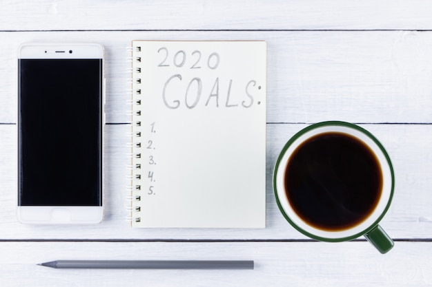 2020 new year goals, plan, action text on notepad on white wooden boards.
