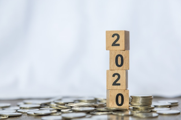 2020 new year, money and business concept. close up of stack of number wooden block toy on pile of coins