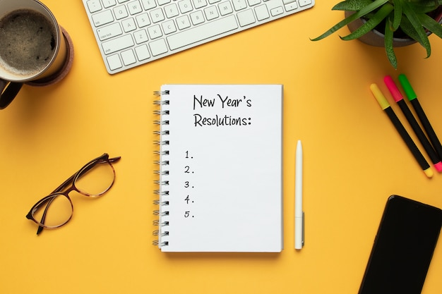 2020 new year notebook with list of resolutions and objects on yellow background