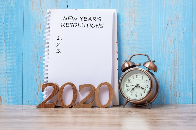 2020 new year resolutiions with notebook, retro alarm clock and wooden number.