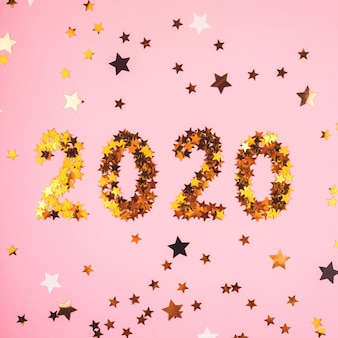 2020 new year symbol of gold confetti on pink background.