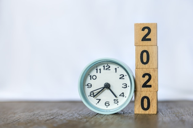 2020 new year and time . close up of round clock and stack of wood number blocks on wooden table and white .