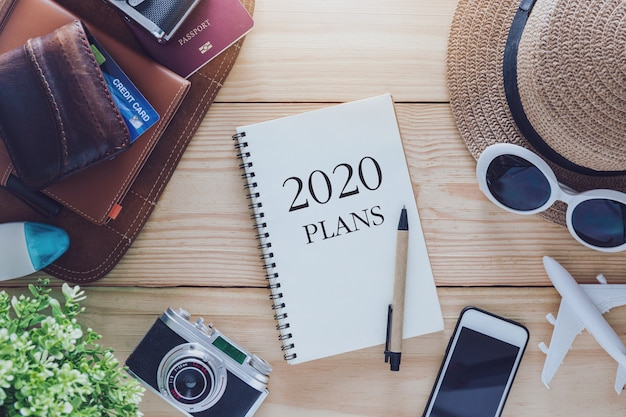 2020 note book plans with hat, sunglasses, phone, camera and aeroplane