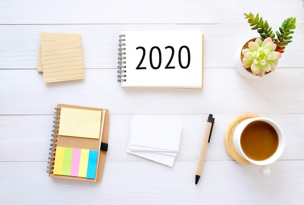 2020 on notebook paper and blank notepad organizer businesscard coffee pencil on wood background