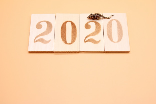 2020 number lined with wooden figures and a little metal mouse next to it.