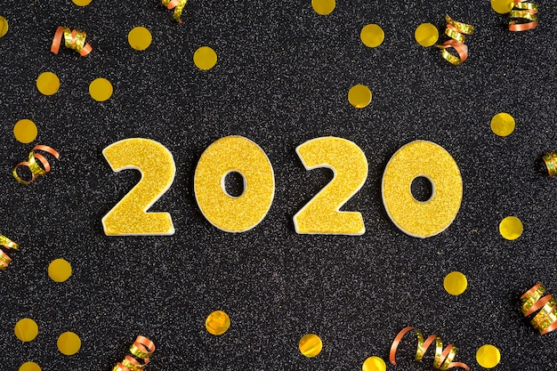 2020 numbers decorated with gold sequins,  ribbon, ball on shiny black .