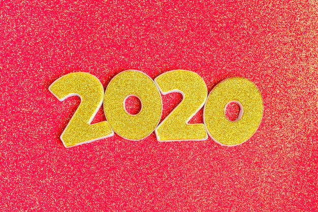 2020 numbers decorated with gold sequins on shiny coral red .