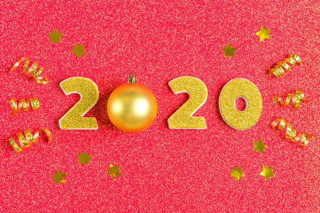 2020 numbers decorated with gold sequins, stars, ribbon, ball on shiny coral red .