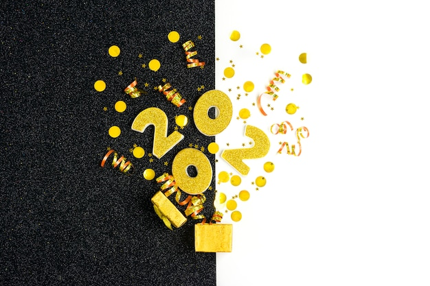 2020 numbers decorated with gold sequins, stars, ribbon, hat cap, gift box, ball on shiny black and white .