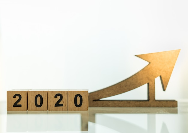2020 planning,  business and goal concept. close up of wooden number blocks with wood arrow icon diecut with copy space.