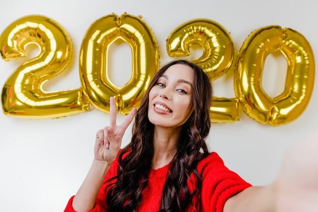 2020年の新年の風船の前で面白いselfieを作る赤いセーターで美しい女性