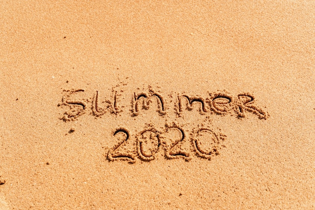 2020 summer lettering on the beach with wave and clear blue sea. travelling on summer vacation