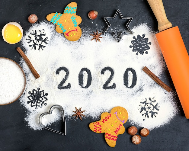 2020 text made with flour with decorations on a black background.