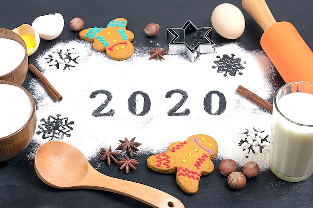 2020 text made with flour with decorations on black . flat lay.