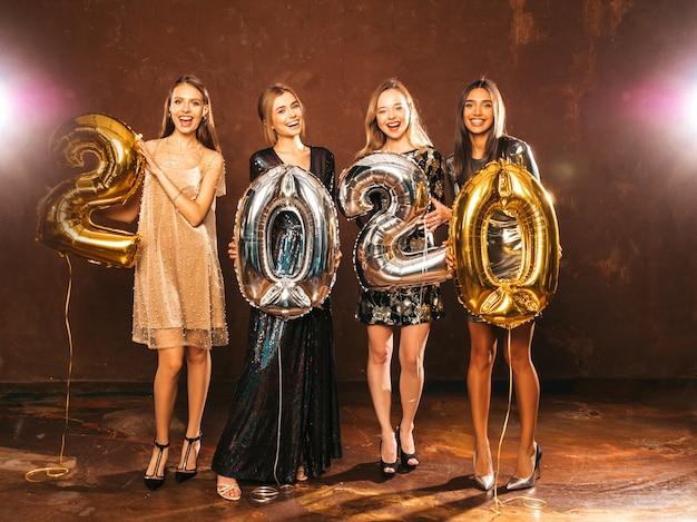 新年を祝う美しい女性。金と銀の2020年の風船を保持しているスタイリッシュなセクシーパーティードレスで幸せな豪華な女の子、大ve日パーティーで楽しんでいます。休日のお祝い。魅力的なモデル