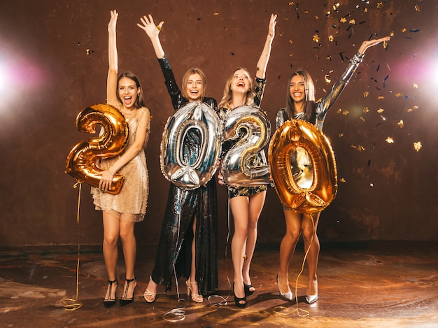 新年を祝う美しい女性。金と銀の2020年の風船を保持しているスタイリッシュなセクシーパーティードレスで幸せな豪華な女の子、大ve日パーティーで楽しんでいます。休日のお祝い。手を上げる