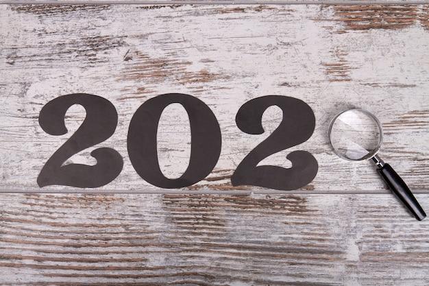 2020 с лупой на деревянном столе