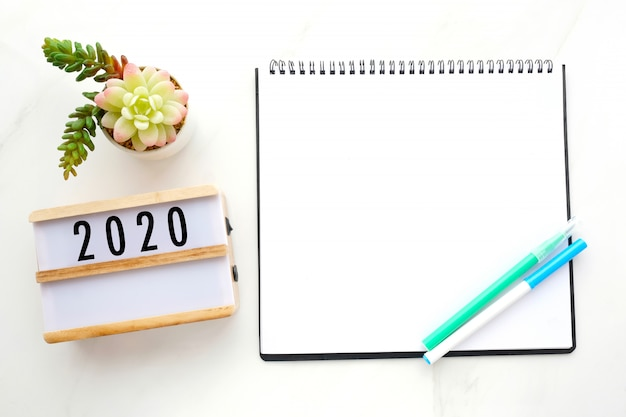 2020 on wood box blank notebook paper on white marble table background