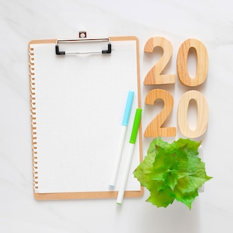 2020 wooden letters and blank notebook paper on white marble table background