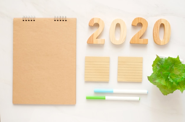 2020 wooden letters and blank notebook paper with copy space for text new year background banner concept