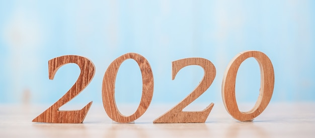2020 wooden number on blue table background with copy space for text.