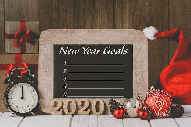 2020 wooden text and alarm clock with christmas ornaments and new year's goals list written on chalkboard