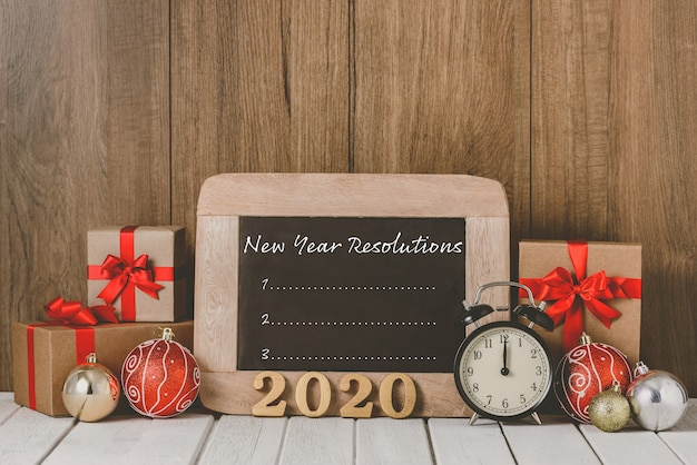 2020 wooden text and alarm clock with christmas ornaments and new year's resolutions list written on chalkboard