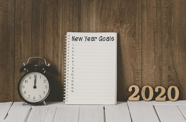 2020 wooden text and new year's goals list written on notebook with alarm clock