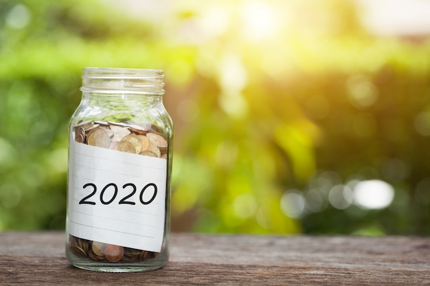 2020 word with coin in glass jar.