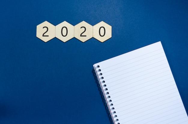 2020年には、新しいメモ帳と白いメモ帳で木製の六角形に書かれた、新しい年と新しい年の決議の概念図が描かれています。コピースペースと青いスペース。