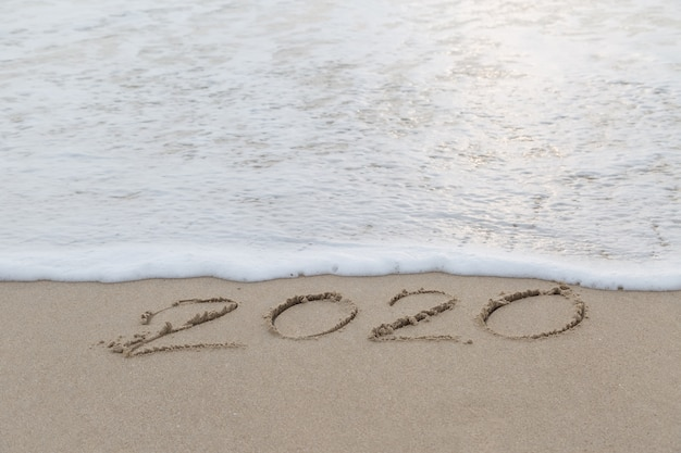 2020 written in the sand on the beach before new year