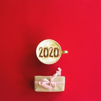 2020 year concept inscription on a cup of cappuccino on red.