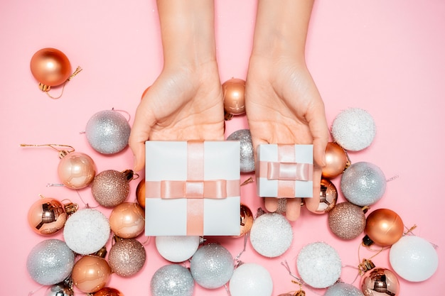 2020年の新年の構成。スタイリッシュな装飾のコンセプトデザイン、クリスマスツリーラウンドおもちゃ、両手ピンクのギフトボックス